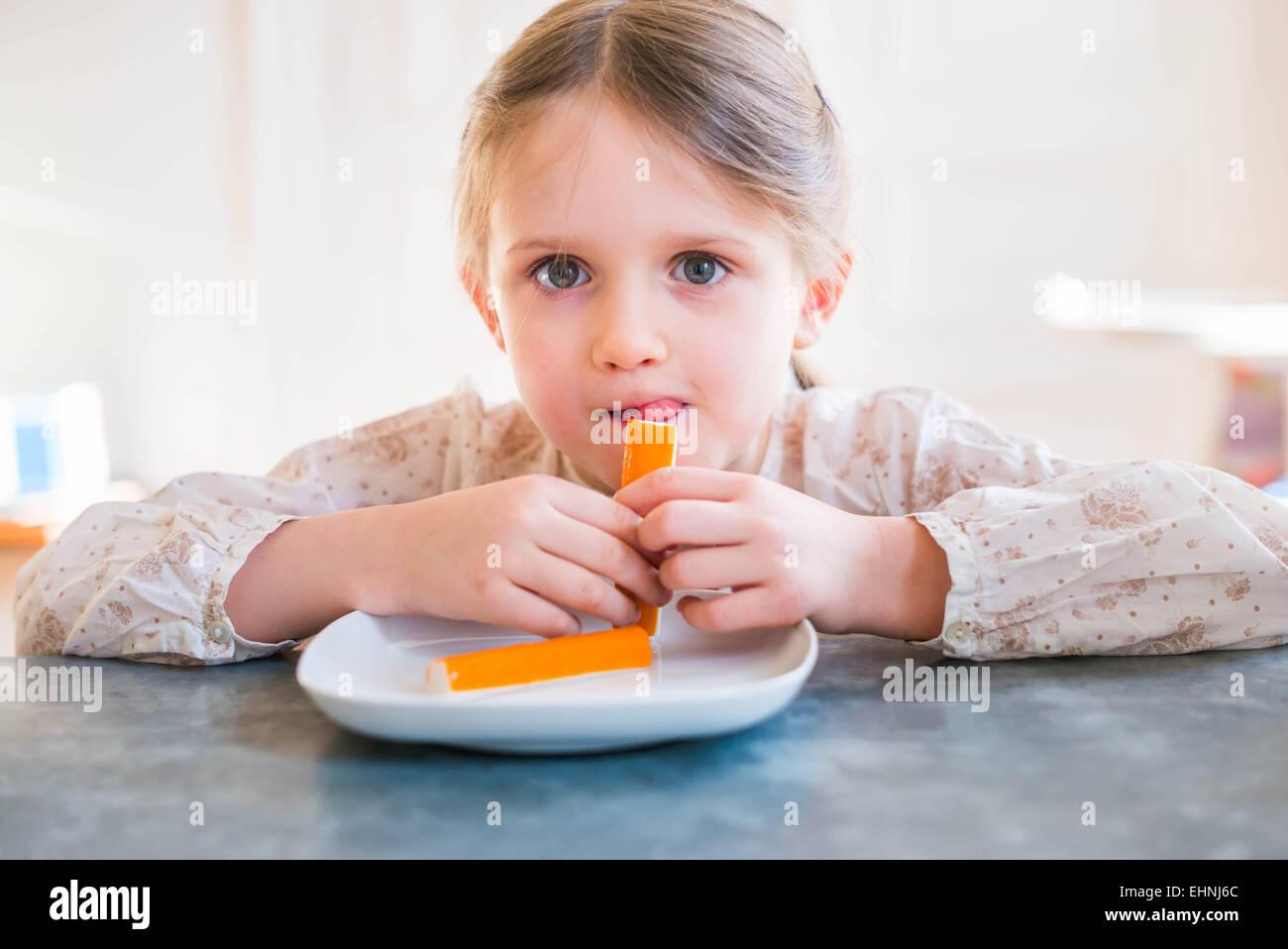 Niña de cinco años el surimi de comer. Foto de stock