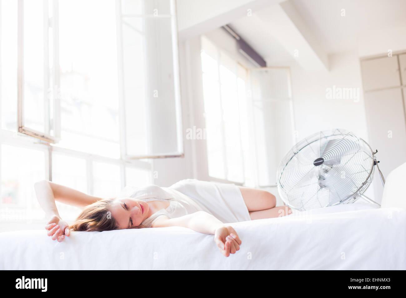 Mujer en frente de un ventilador eléctrico. Imagen De Stock