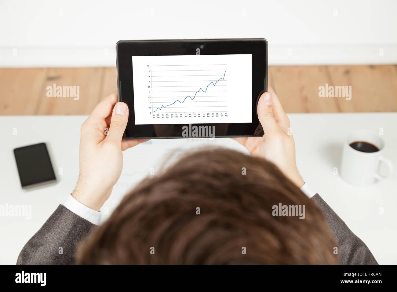 Hombre sujetando tablet con creciente gráfico en tablet Imagen De Stock