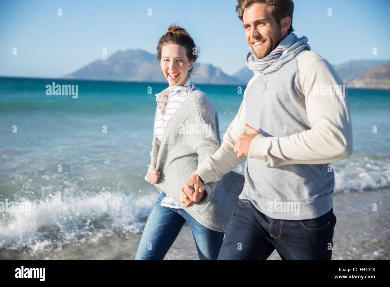 Pareja joven tomados de la mano y caminar en la playa Foto de stock