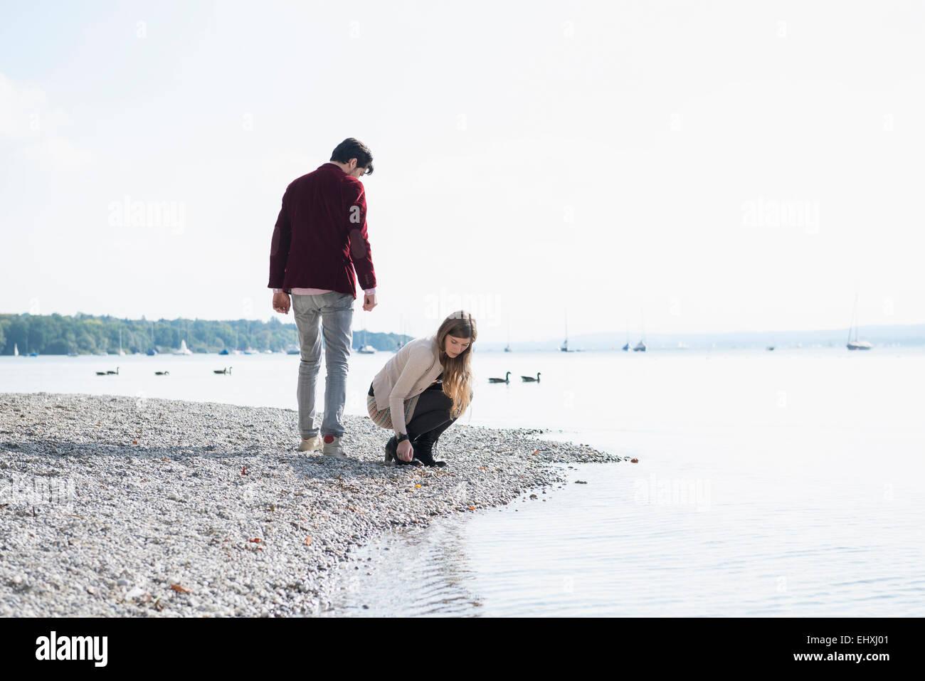 Pareja joven Lake Shore recogiendo guijarros Imagen De Stock