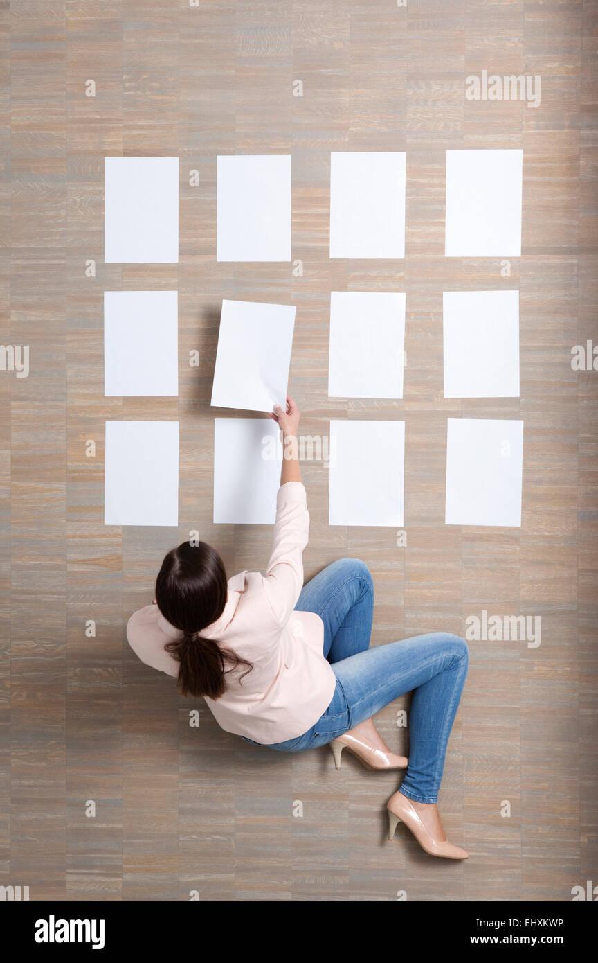 La empresaria sentado en suelo organizar hojas de papel en blanco Foto de stock