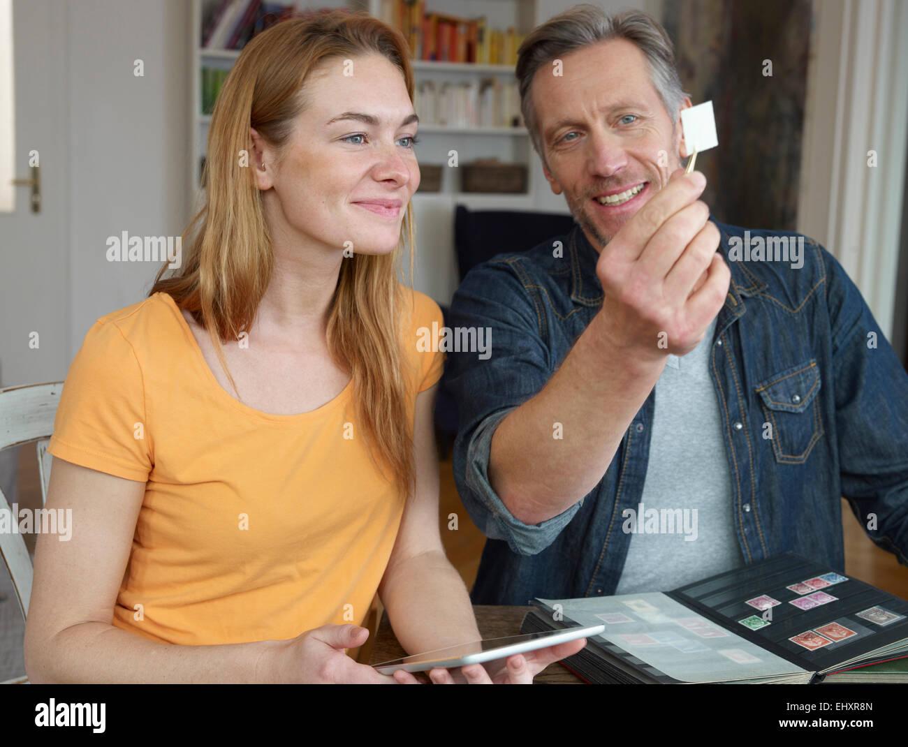 d607ca6edc Hombre maduro y mujer joven mirando a través de la colección de sellos