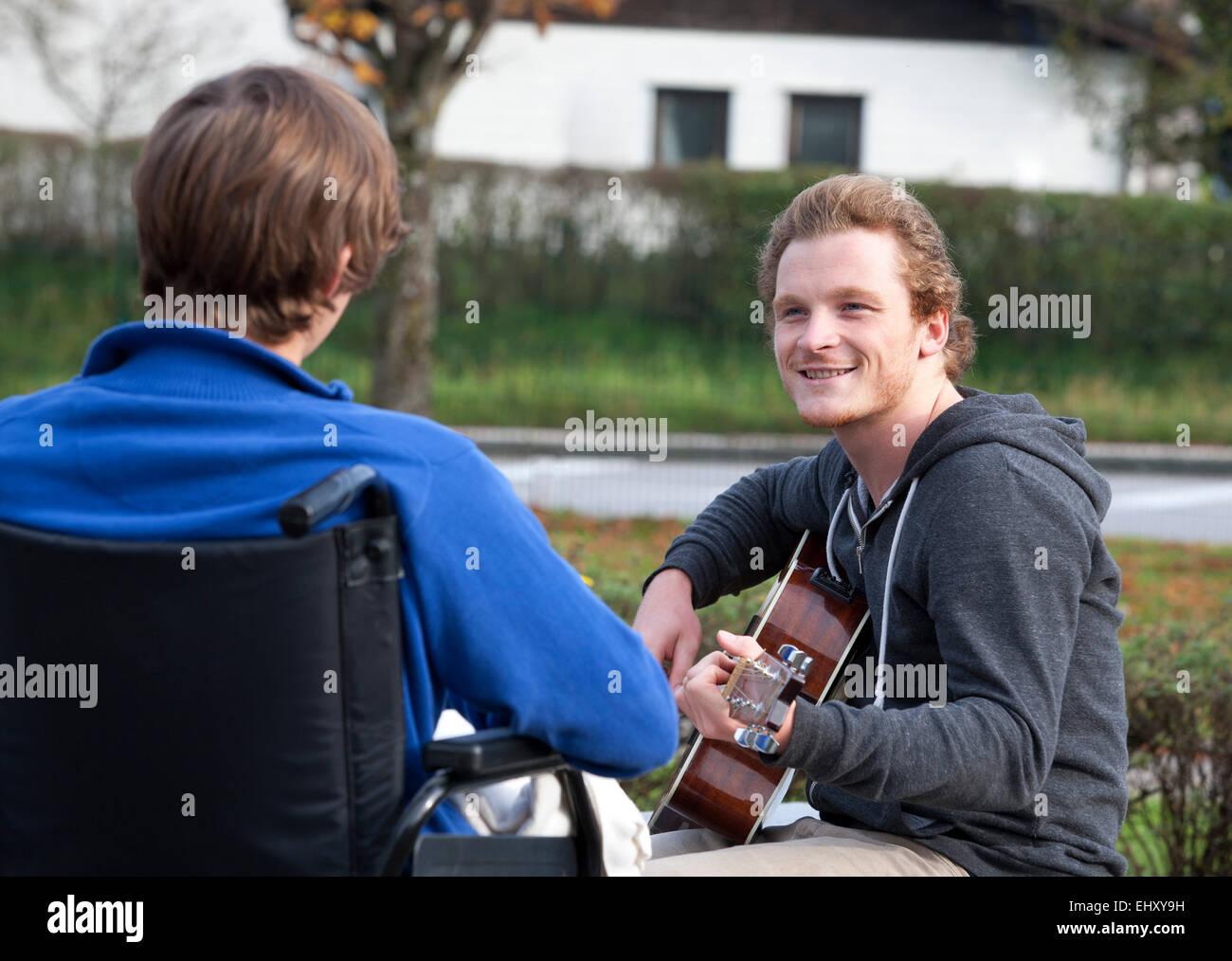Un joven usuario de silla de ruedas escuchando guitarrista Foto de stock