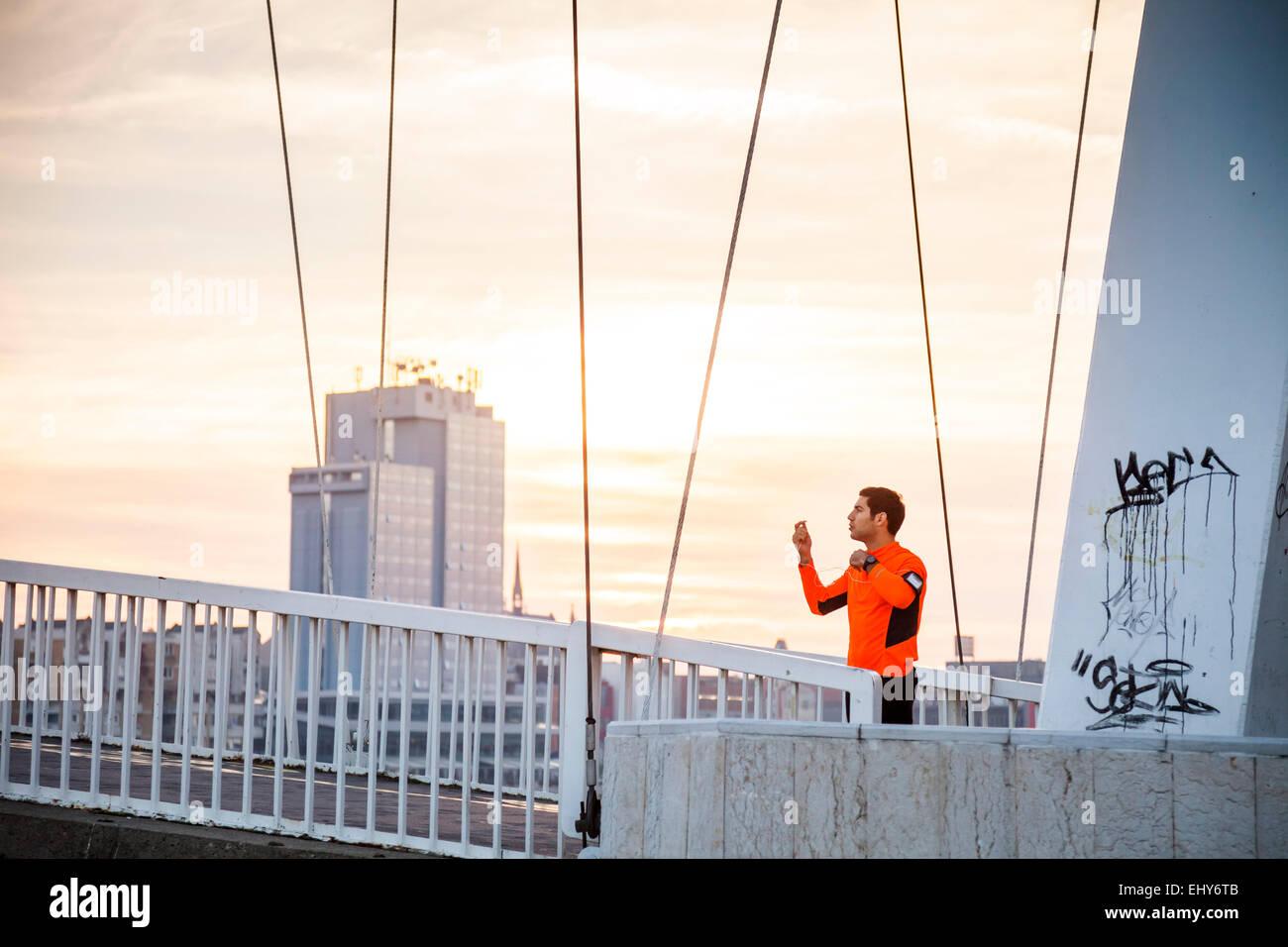 Deslizadera macho en el puente se toma un descanso contra skyline Imagen De Stock