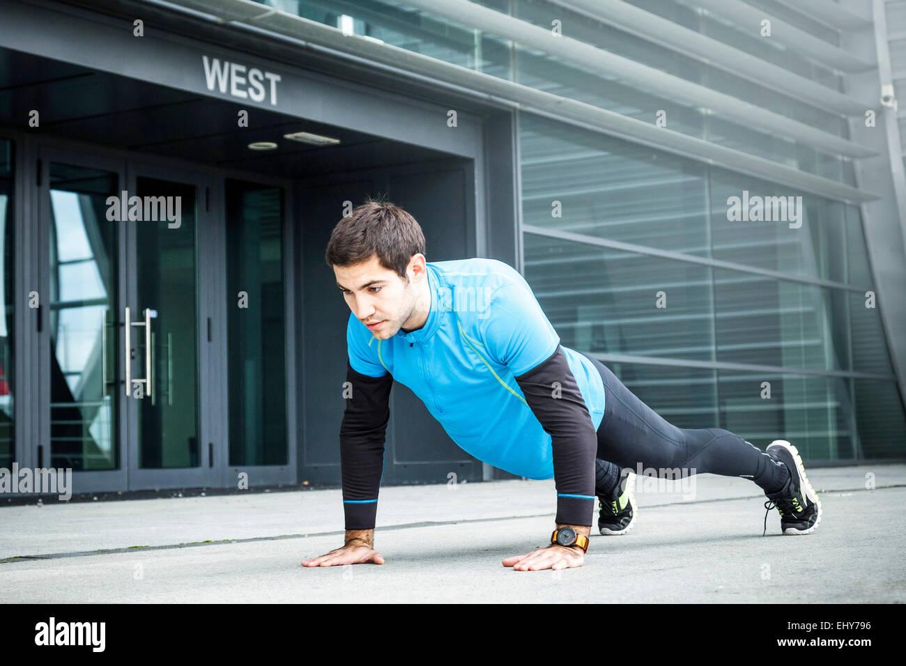 Deslizadera macho haciendo push-ups en la ciudad Imagen De Stock