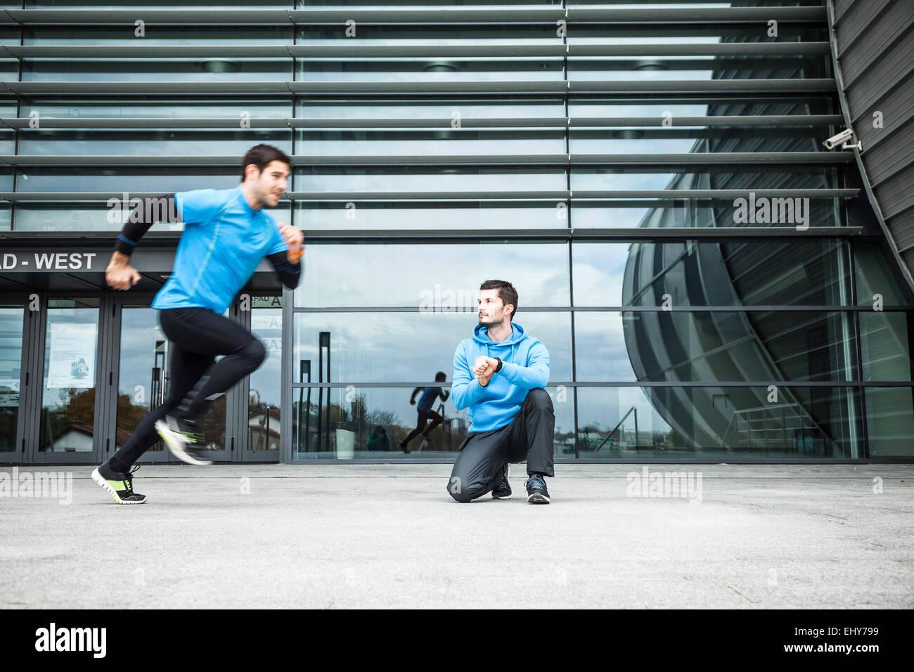 Los corredores masculinos haciendo entrenamiento de sprint en la ciudad Imagen De Stock