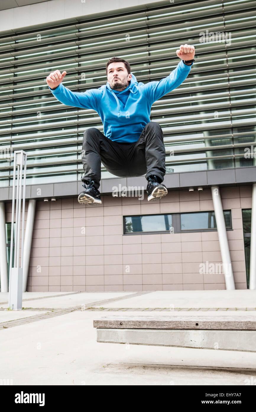 Deslizadera macho saltando brazos levantados Imagen De Stock
