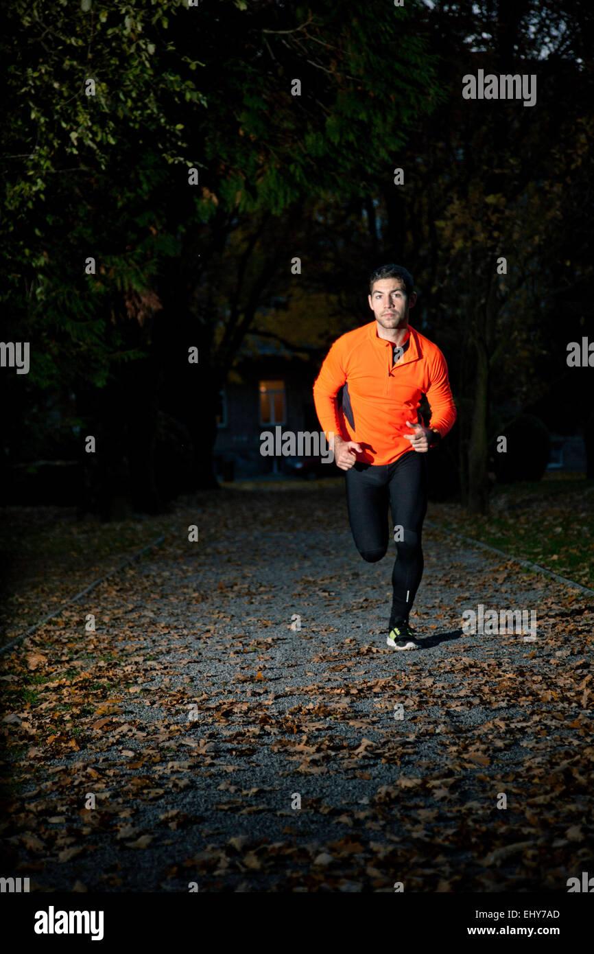 Deslizadera macho haciendo un entrenamiento de sprint en penumbra Imagen De Stock