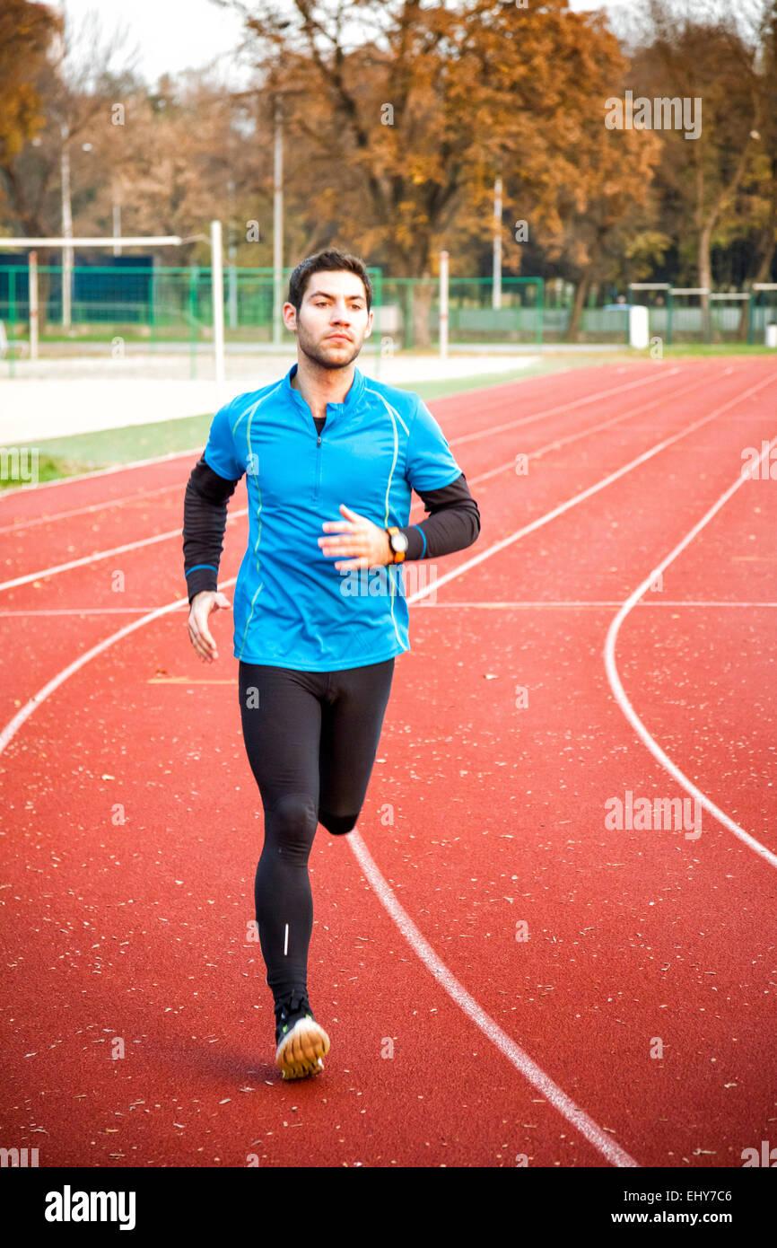 Hombres runner jogging en pista de atletismo Imagen De Stock