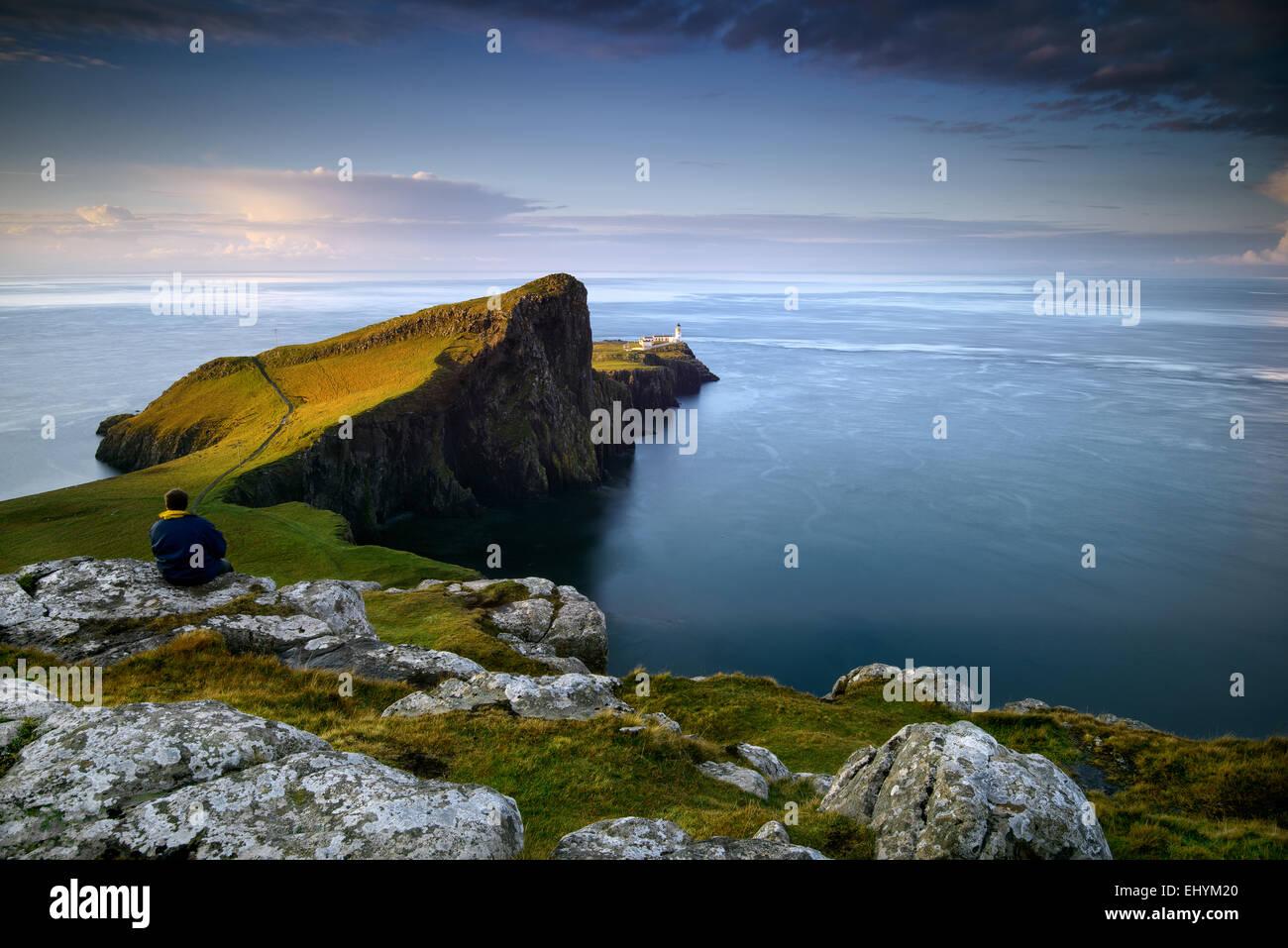 Mitad hombre adulto sentado en una roca mirando al mar en Neist Point, Escocia Imagen De Stock