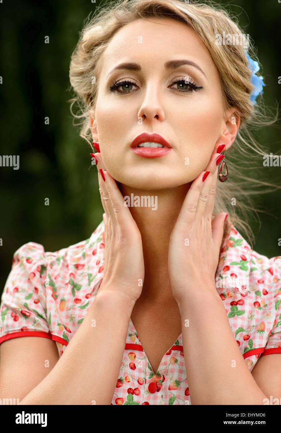 Retrato de una mujer adulta media sosteniendo sus manos a su cara Imagen De Stock