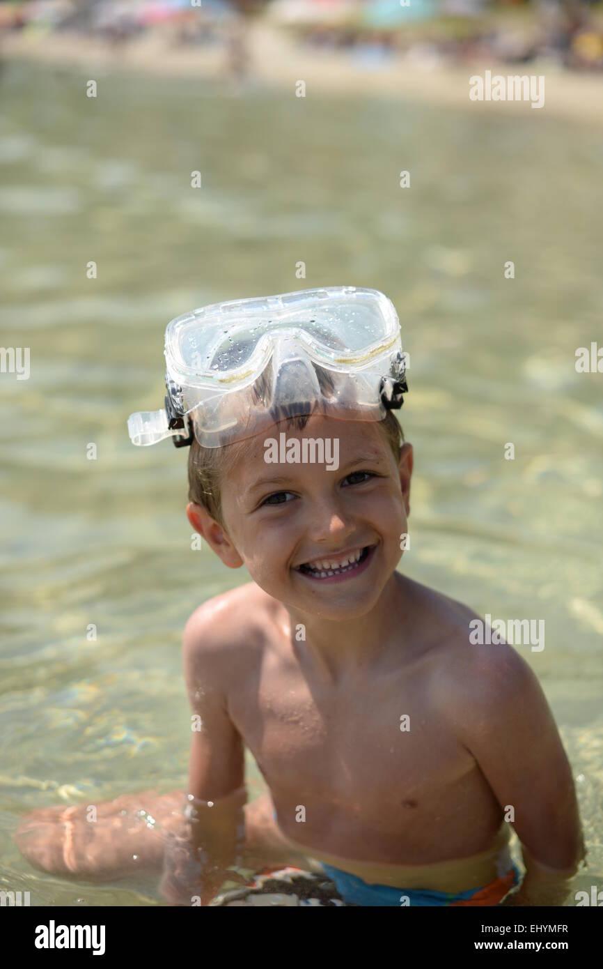 Retrato de un sonriente muchacho sentado en el mar gafas protectoras sobre su cabeza. Imagen De Stock