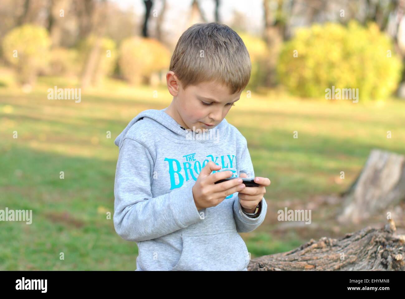 Niño que jugaba en el dispositivo móvil en el parque Imagen De Stock