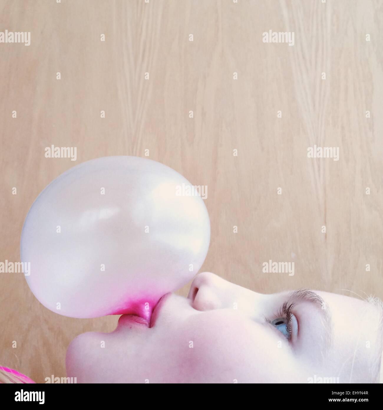 Retrato de una niña soplando una burbuja de chicle Imagen De Stock