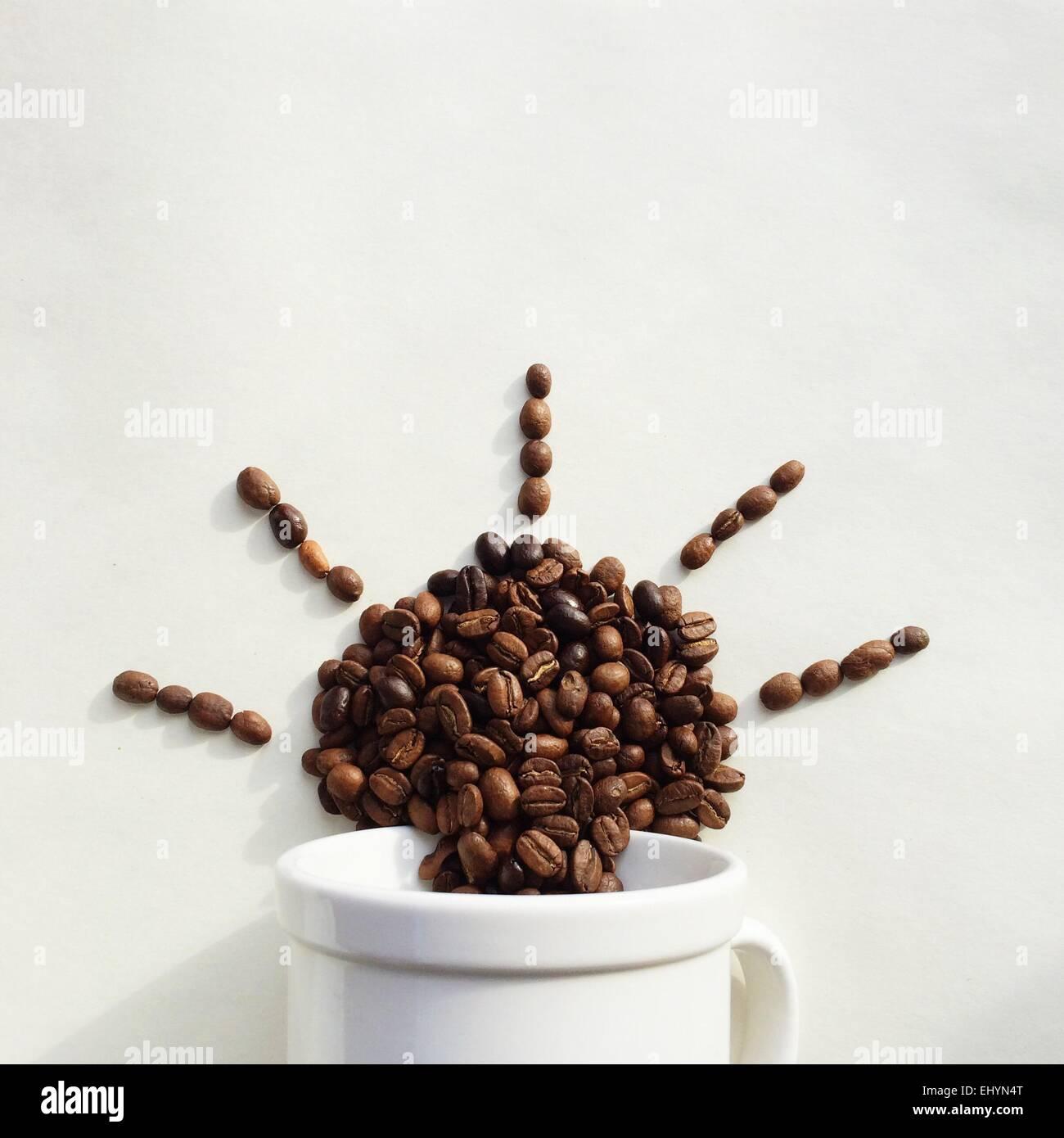 Los granos de café que sale de una taza en la forma del sol Imagen De Stock