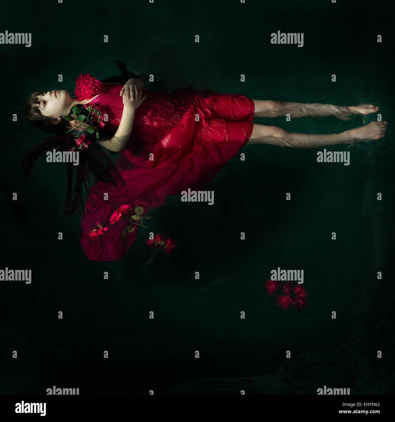 Niña en un vestido rojo flotando en el agua rodeado de rosas rojas Foto de stock