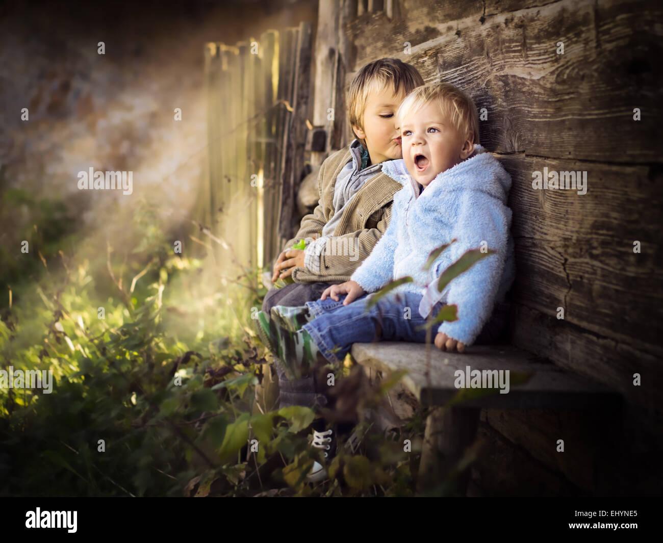 Dos hermanos sentados sobre una pared divirtiéndose Imagen De Stock