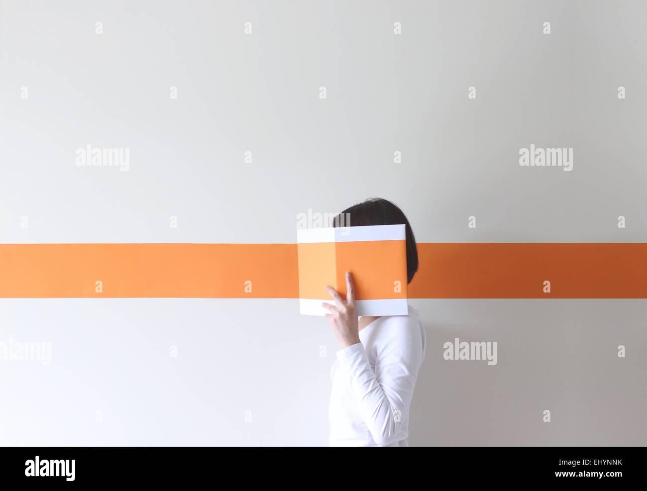 Vista lateral de una mujer madura, ocultando su rostro detrás de un libro Imagen De Stock