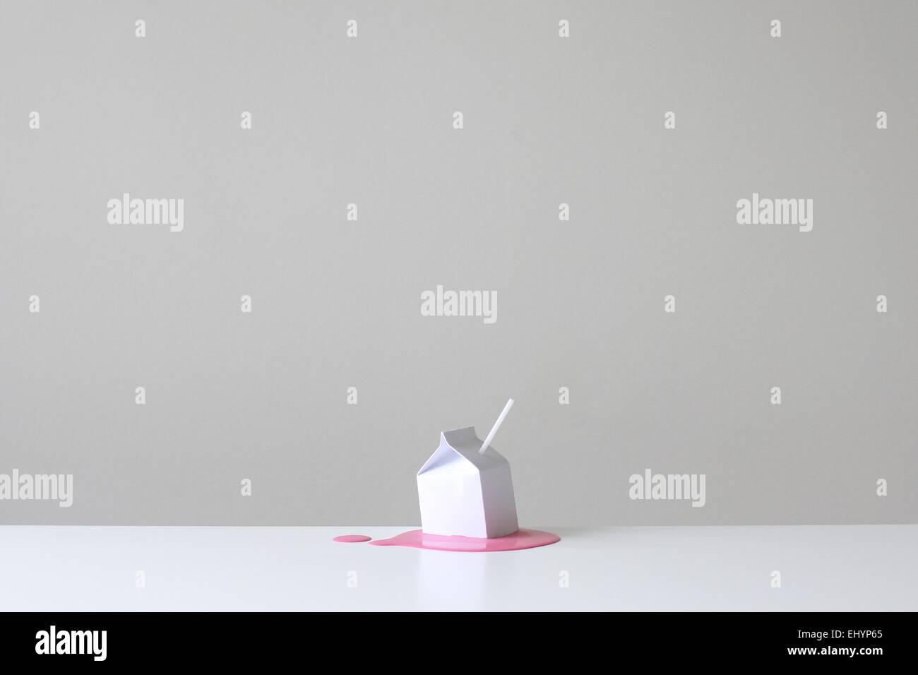 Cartón de leche conceptual con paja en un pool de rosa fresa millk Imagen De Stock