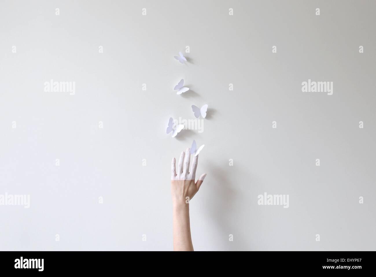 La mitad de una mano pintada en blanco alcanza para mariposas de papel contra la pared blanca Imagen De Stock