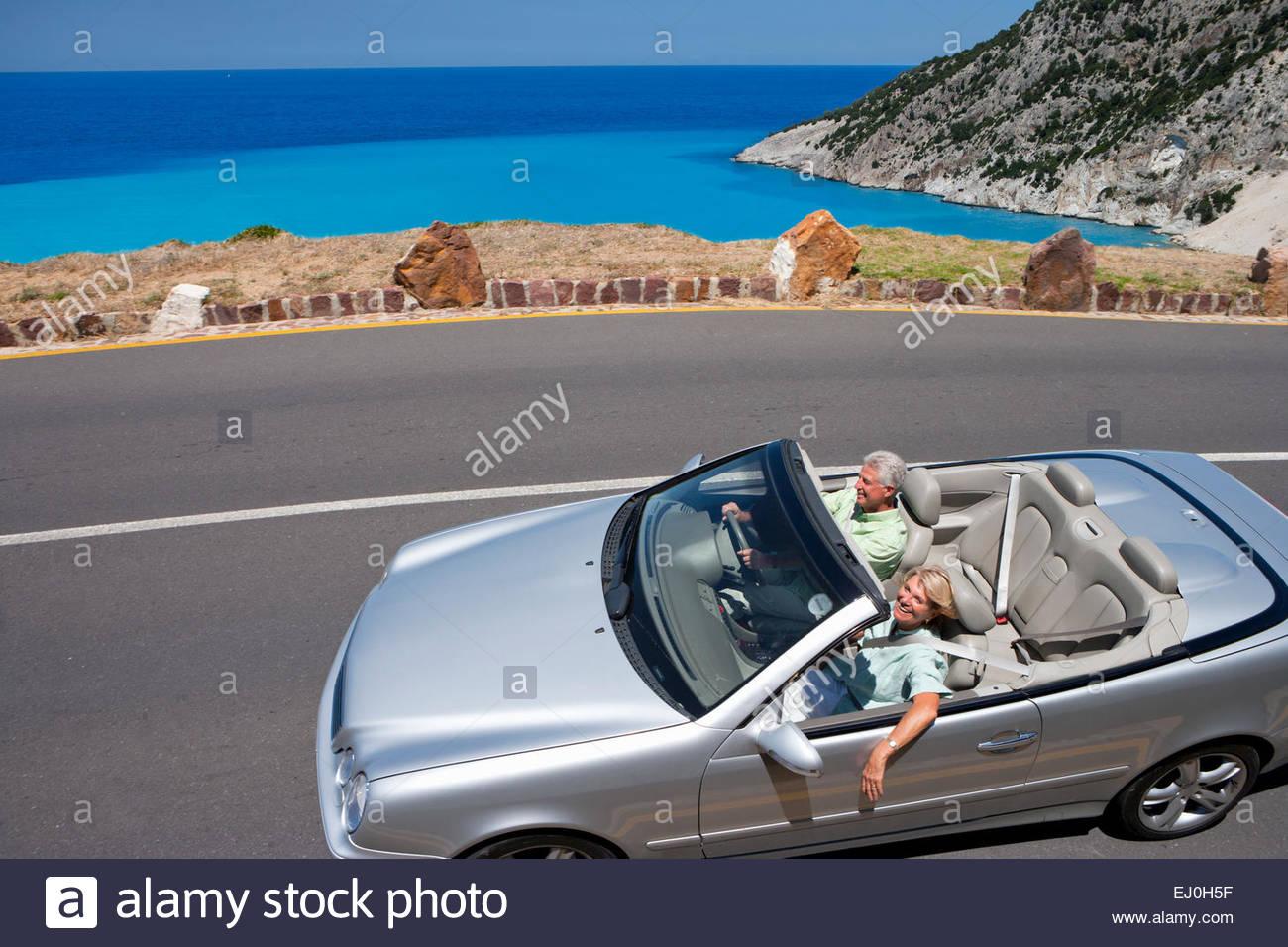 Pareja senior convertibles conducir el coche por la carretera costera Imagen De Stock