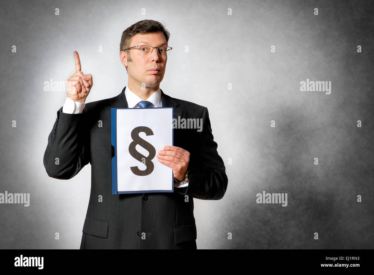 Empresario de traje oscuro tiene una carpeta con un gran signo de párrafo Foto de stock