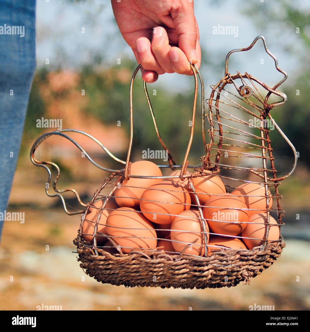 Primer plano de la mano de un joven hombre caucásico llevando una gallina metálica oxidada en forma de Imagen De Stock