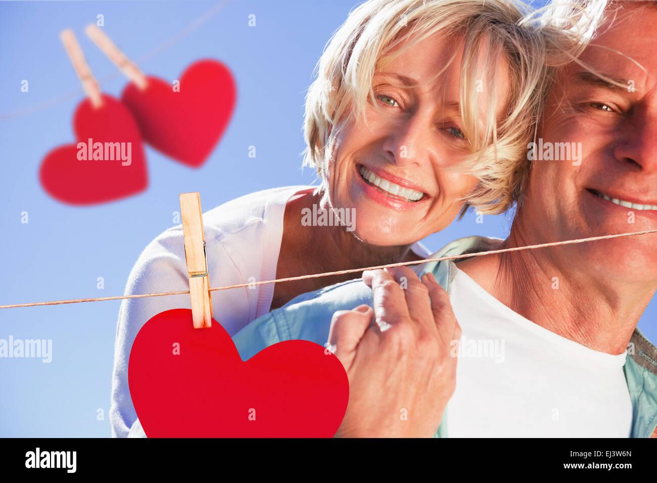 Imagen compuesta de feliz senior hombre dando su pareja un piggy back Imagen De Stock