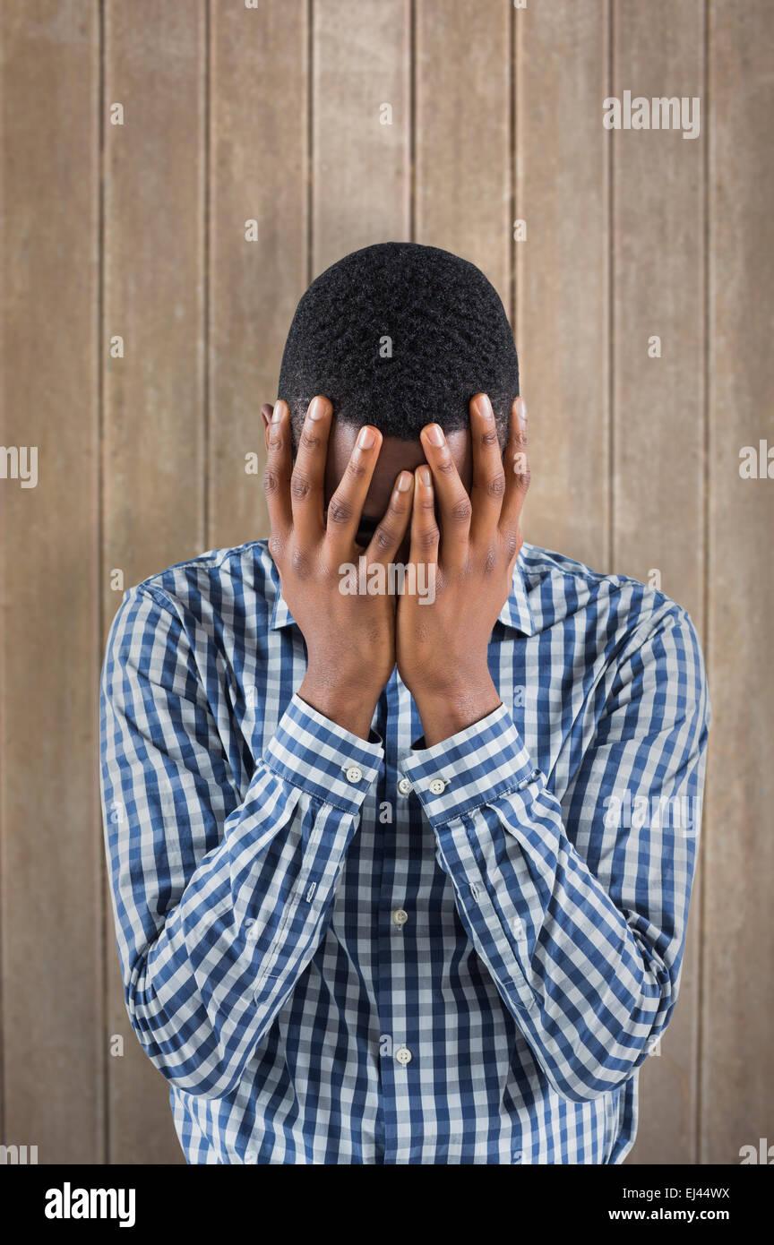 Imagen compuesta de joven empresario con la cabeza entre las manos Imagen De Stock