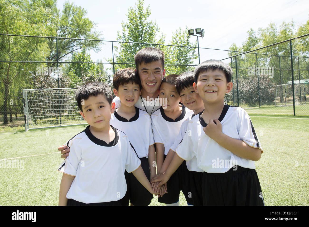 El entrenador de fútbol y los muchachos para alentarnos mutuamente en el campo de fútbol Imagen De Stock