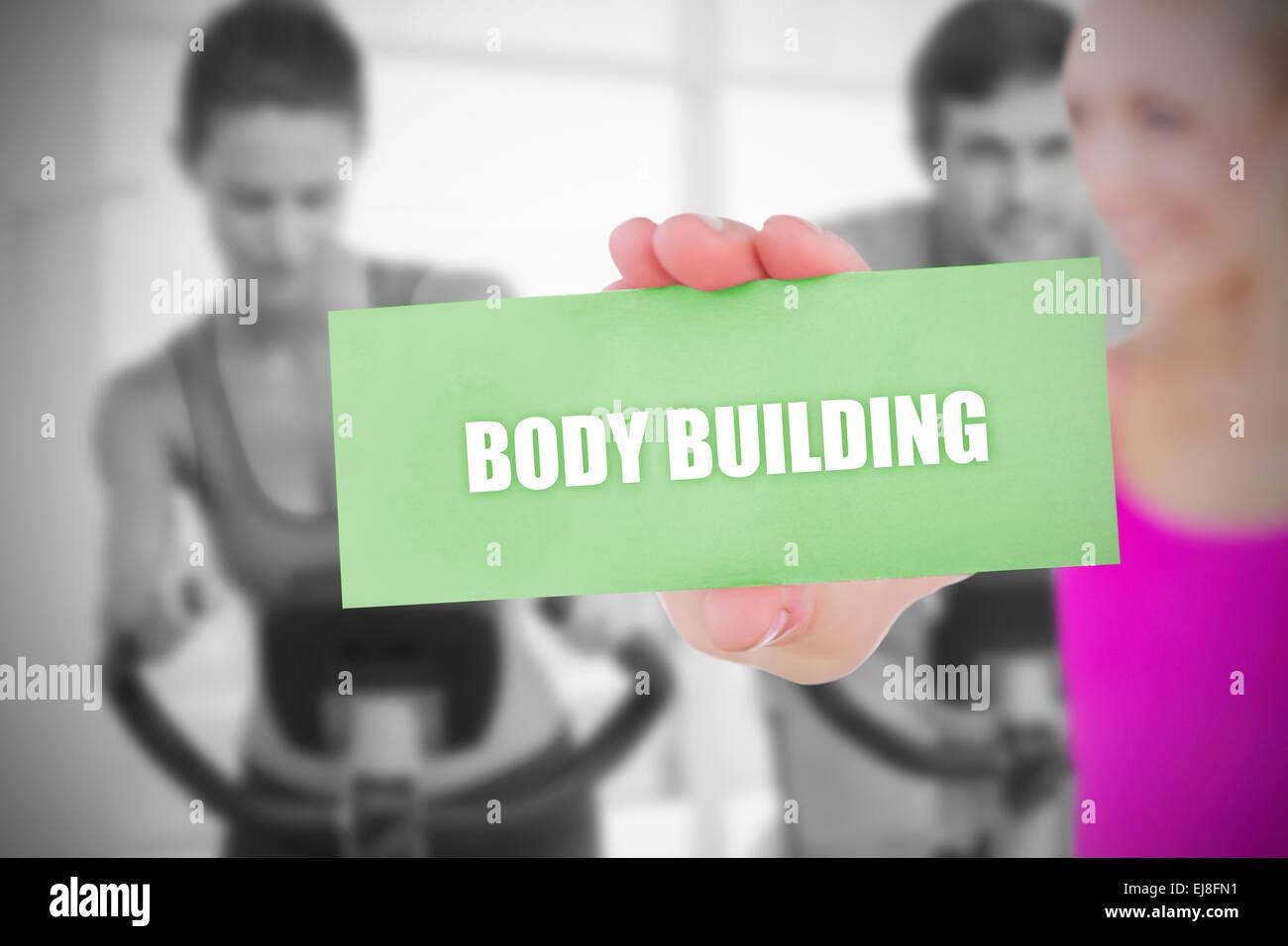Colocar rubia celebración carta diciendo body building Imagen De Stock