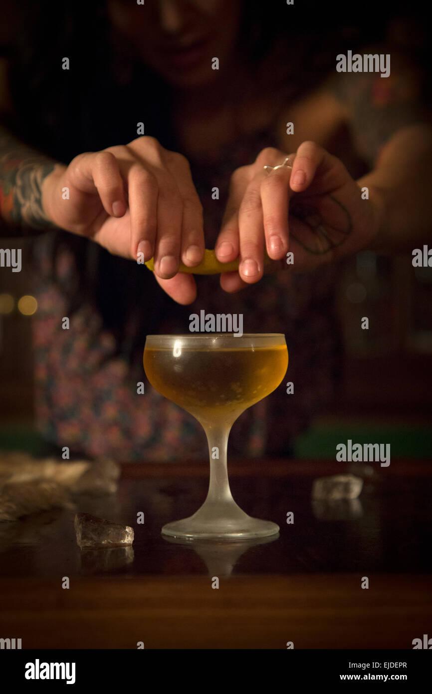 Las manos de una mujer exprimir una rodaja de limón en un vaso de cóctel. Imagen De Stock