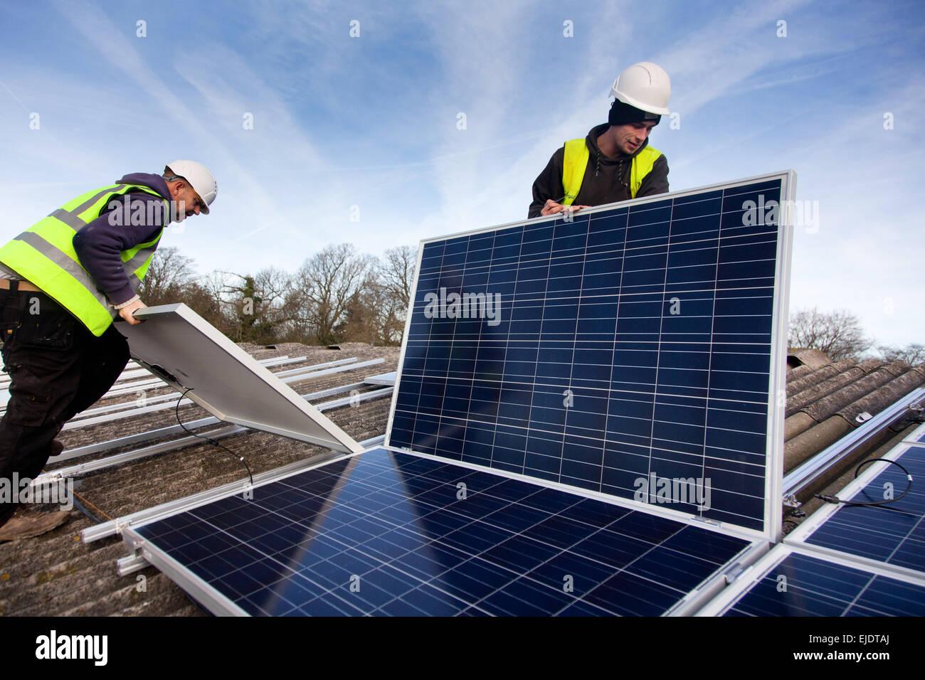 Andy Tyrrell y Jake Beautyman instalar paneles solares en el techo de un granero en Grange Farm, cerca de Balcombe. Imagen De Stock