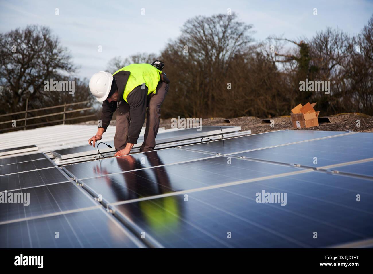 Jake Beautyman instala paneles solares en el techo de un granero en Grange Farm, cerca de Balcombe. La instalación Imagen De Stock