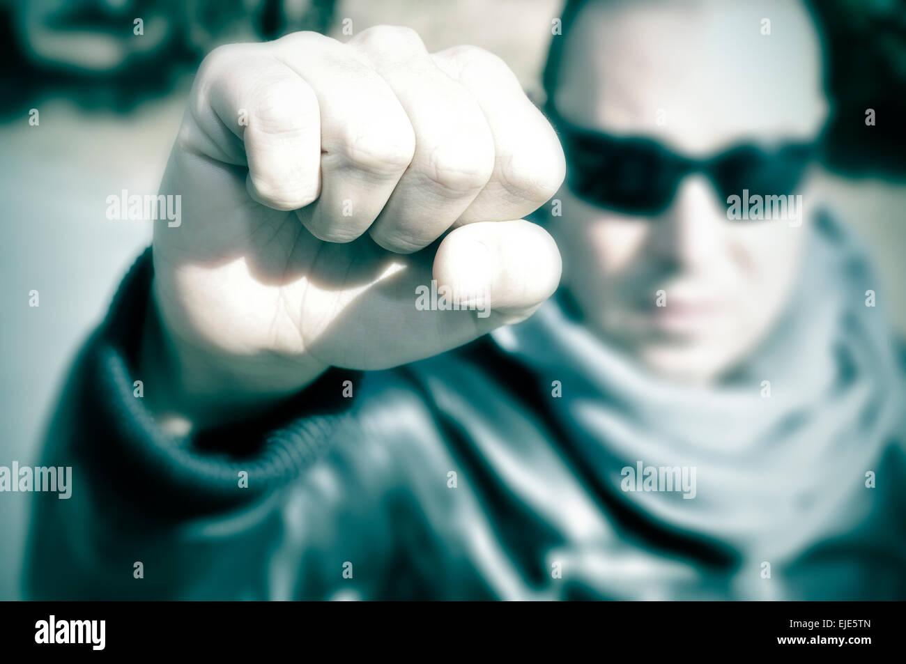 Primer plano de un joven en una protesta levantando su puño y con su rostro desdibujado, con un efecto de filtro Imagen De Stock