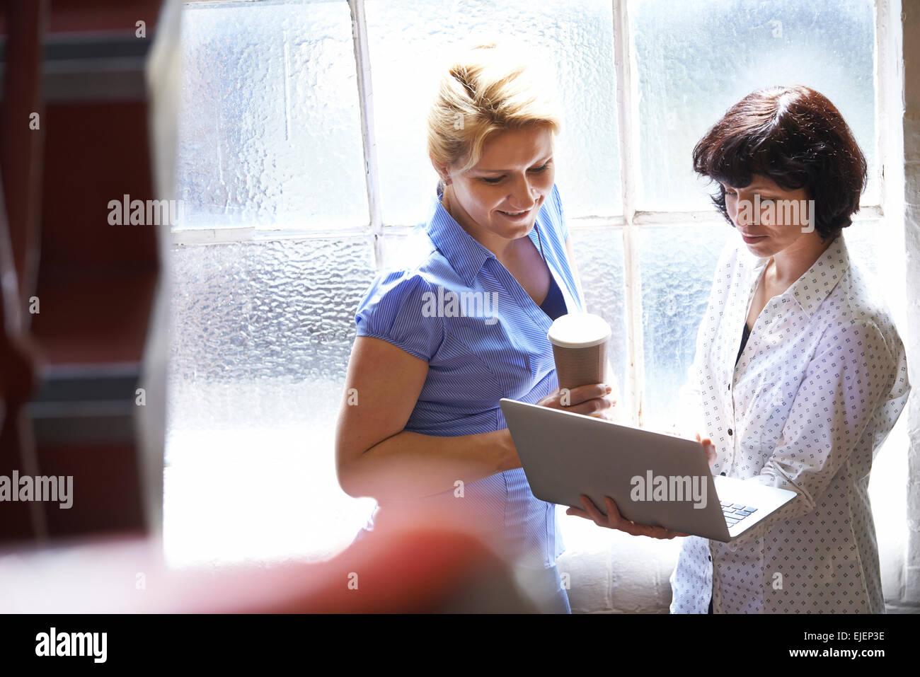 Dos mujeres empresarias habiendo Reunión Informal en Office Imagen De Stock