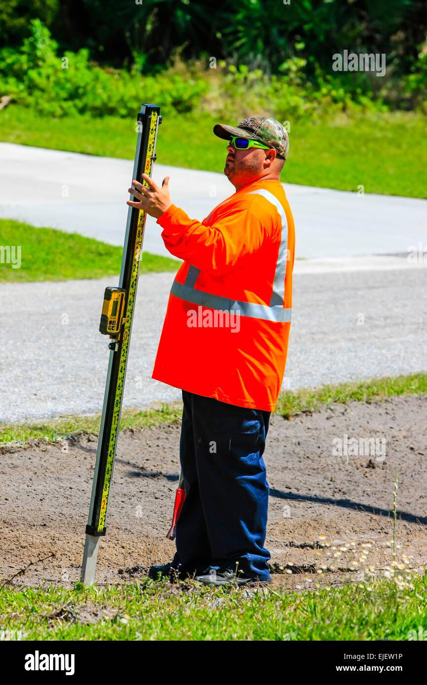 Los trabajadores de mantenimiento de carreteras mediante un manómetro digital de profundidad como la retroexcavadora Imagen De Stock