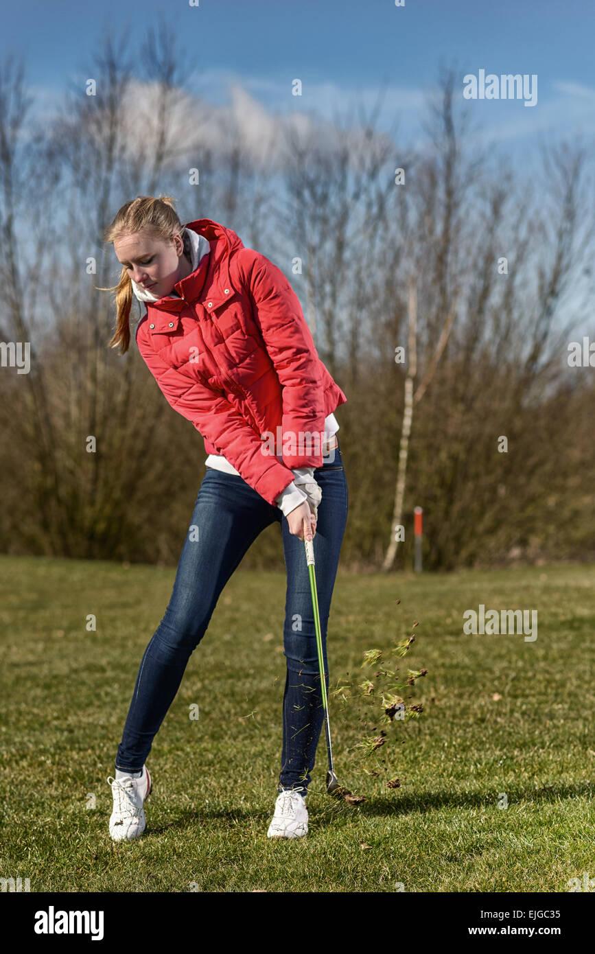 Disparo de longitud completa de una joven golfista, vistiendo chaqueta roja y Skinny Jeans, en el rough, justo después Imagen De Stock