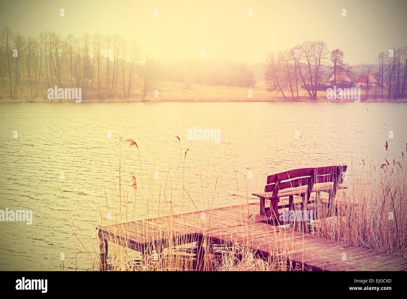 Vintage estilizado foto de un banco de madera en el lago. Foto de stock