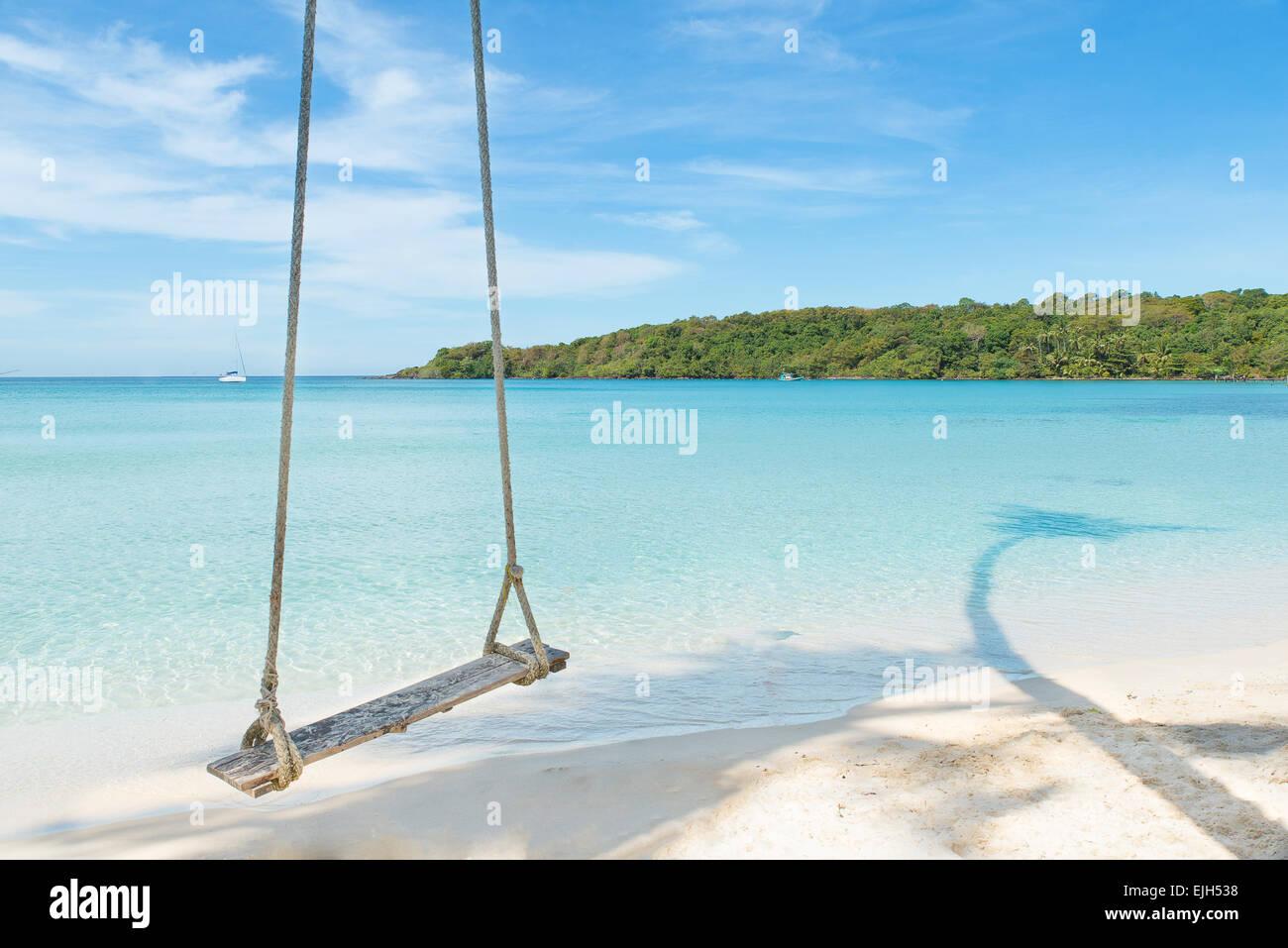 Verano, Viajes, vacaciones y días festivos concepto - Swing colgando del árbol de cocoteros a lo largo de mar en Foto de stock