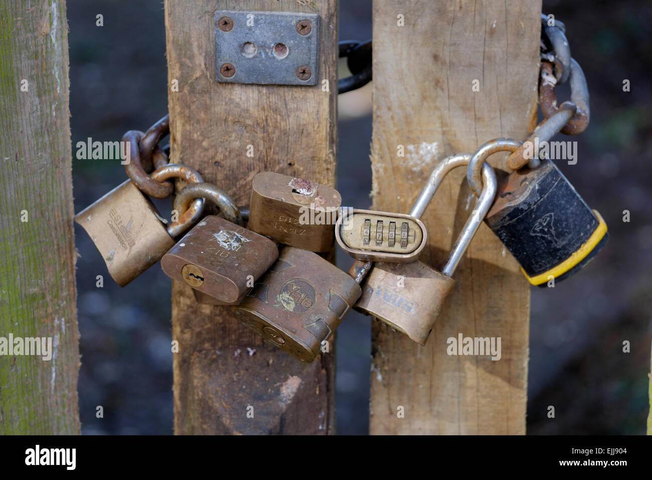 Siete candados y cadenas utilizadas para asegurar puertas de madera Foto de stock