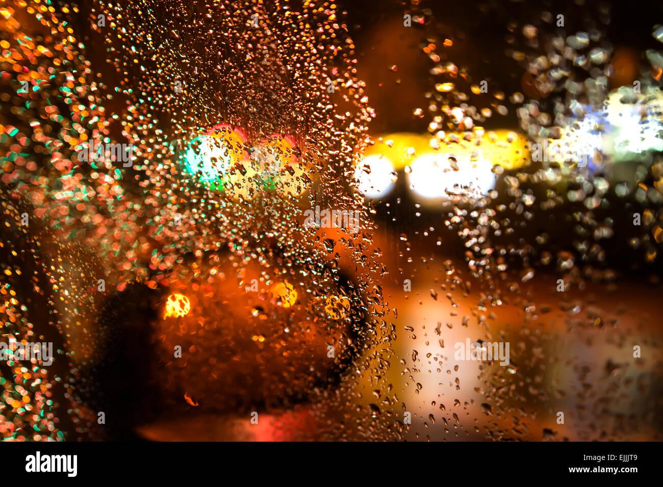 Noche de lluvia a través de la ventanilla del automóvil. Imagen De Stock