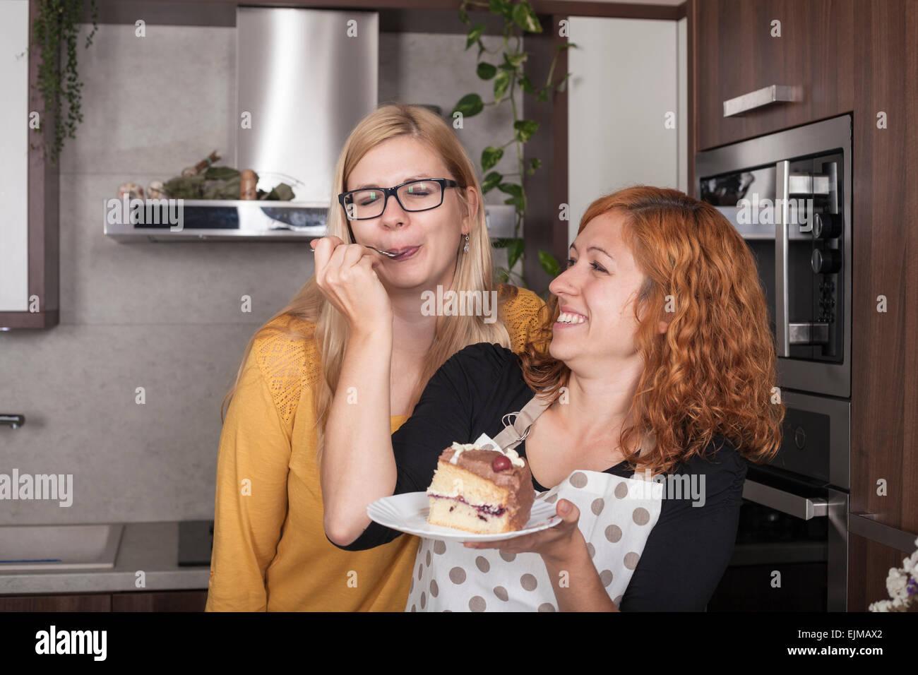 Encantado De Amigas Disfrutando De Una Torta Y Alimentan Mutuamente En La Cocina De Casa