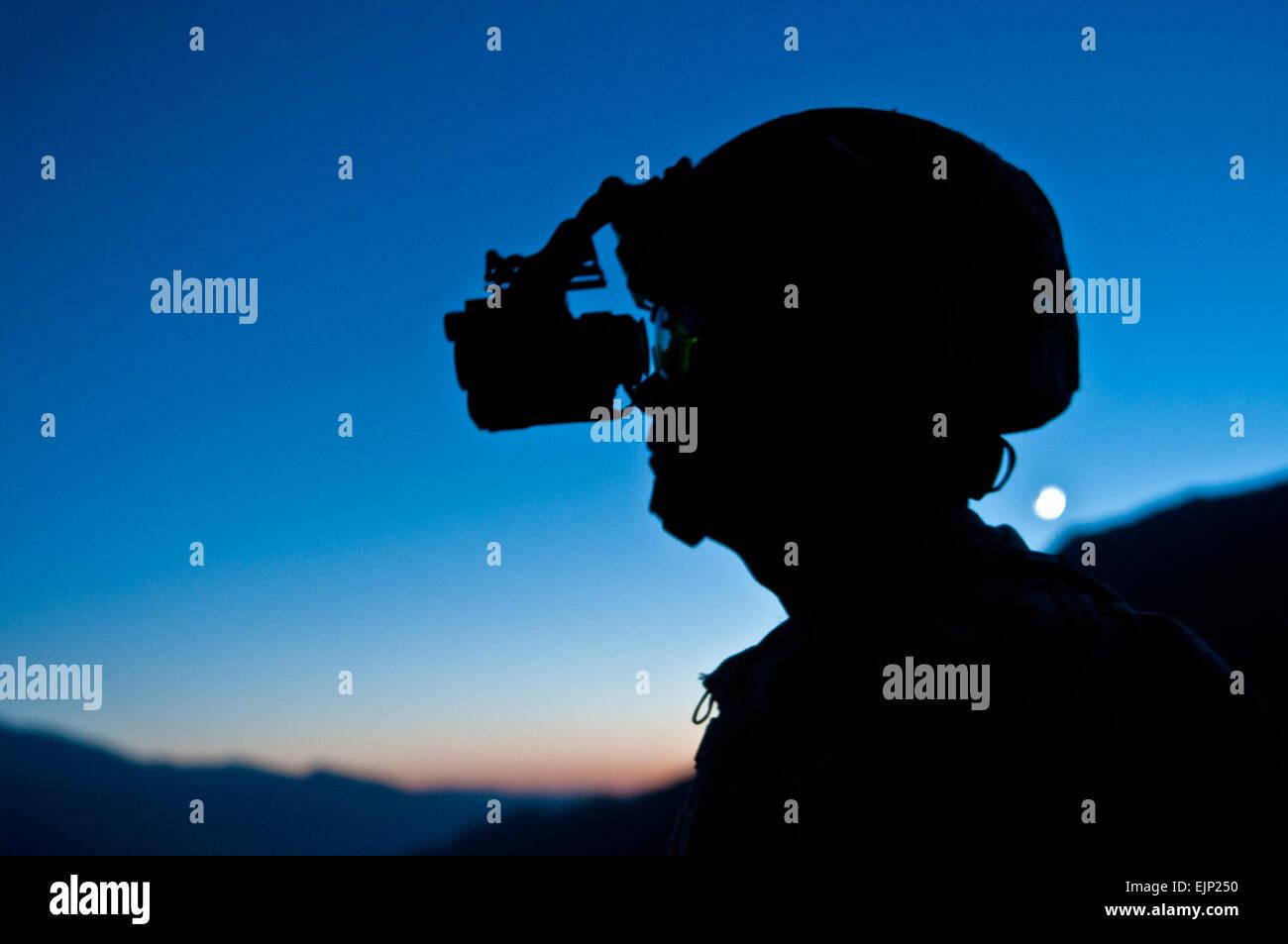 """""""Es bonito ver que esas mismas viejas montañas,"""" dijo el sargento del Ejército de Estados Unidos. James T. Schmidt, un líder de escuadrón de infantería de Decatur, Illinois, asignado a la compañía C, 2º Batallón del 327º Regimiento de Infantería, Fuerza de Tarea sin demora, mientras miraba a través de sus gafas de visión nocturna con la puesta de sol desde lo alto de una colina en el valle Shal en Afganistán oriental provincia de Nuristan, el 8 de noviembre. Este es el segundo combate Schmidt gira a la misma región de Afganistán. El Sargento del Ejército de Estados Unidos. Mark Burrell, 210ª móviles del destacamento de asuntos públicos. Foto de stock"""