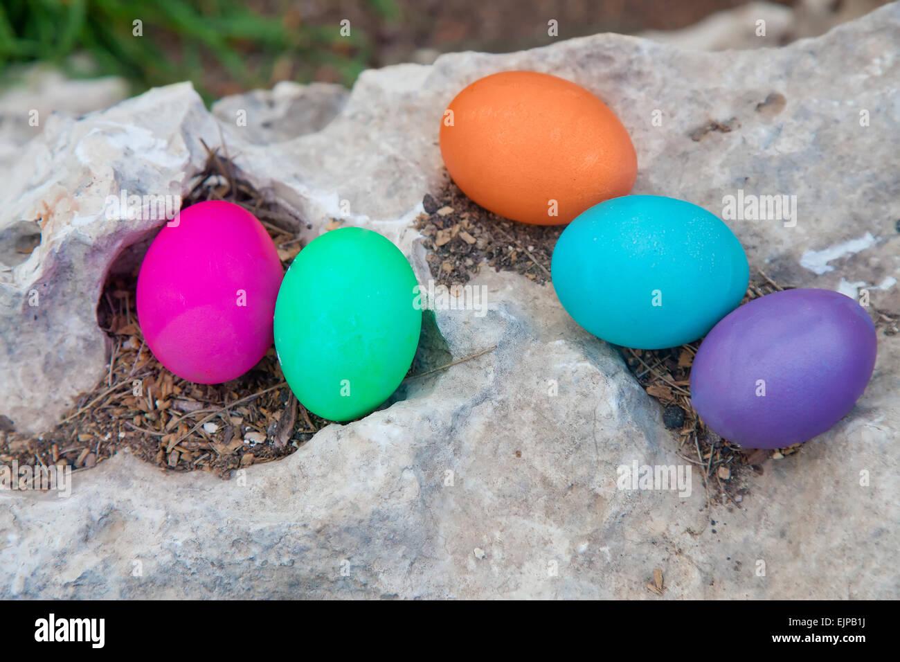 Coloridos huevos sobre una roca - búsqueda del huevo de Pascua concepto Imagen De Stock