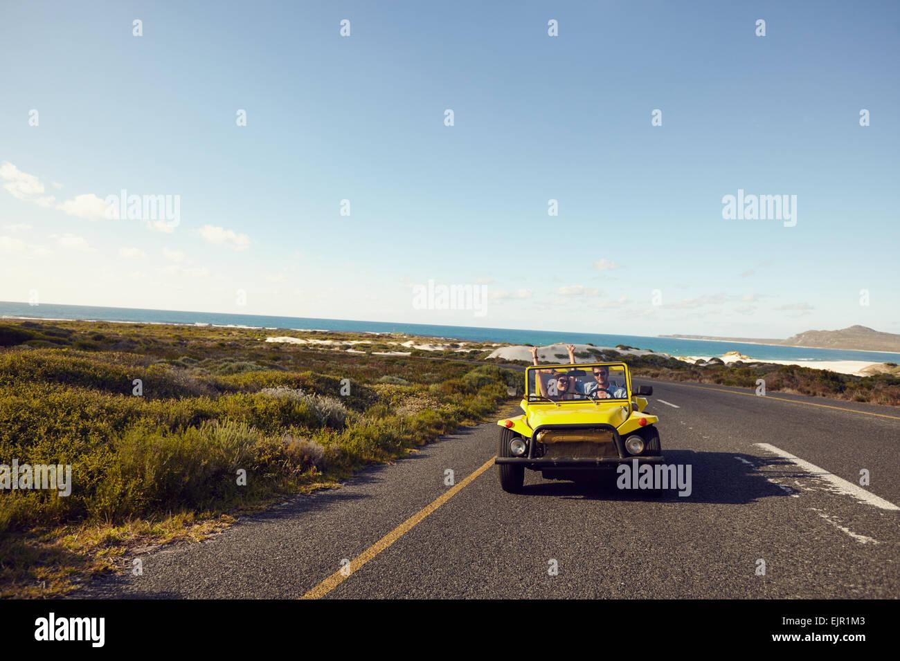 Pareja joven conduciendo por un camino abierto entusiasmado de estar en un roadtrip. Feliz pareja conduciendo un Imagen De Stock