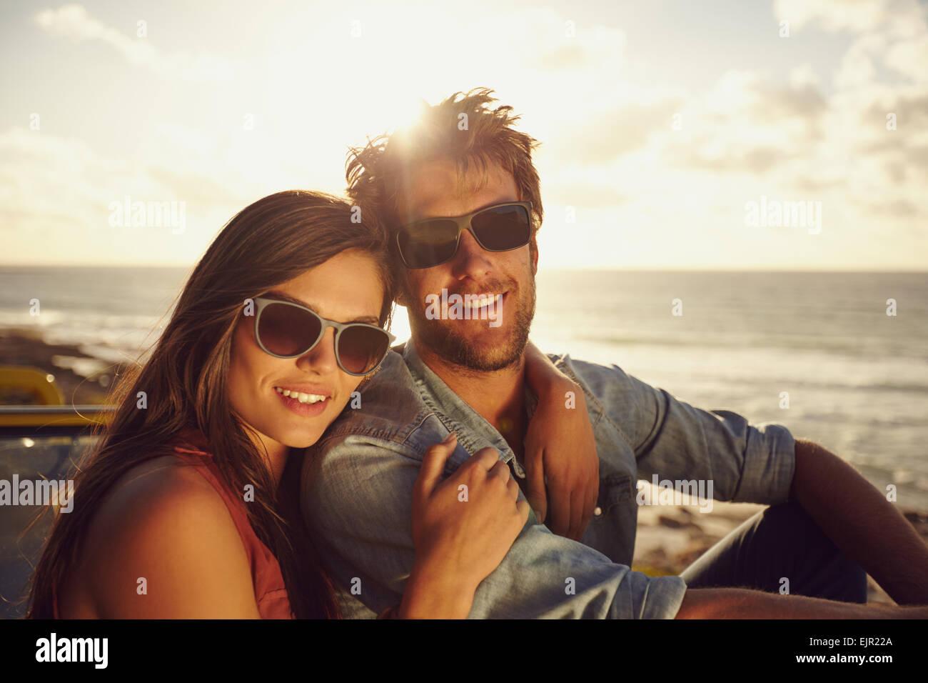 Retrato de hermosa pareja joven con gafas de sol mirando a la cámara mientras estaba en un viaje por carretera. Imagen De Stock