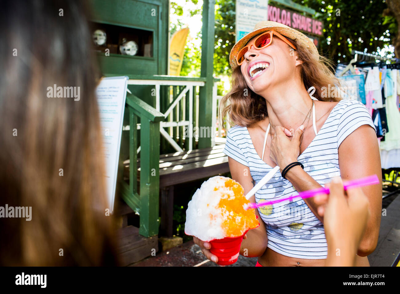 Laughing mujer comiendo shaved ice Foto de stock