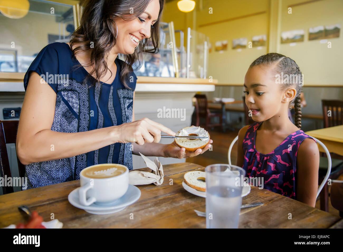 Madre e hija desayunando en el café Foto de stock
